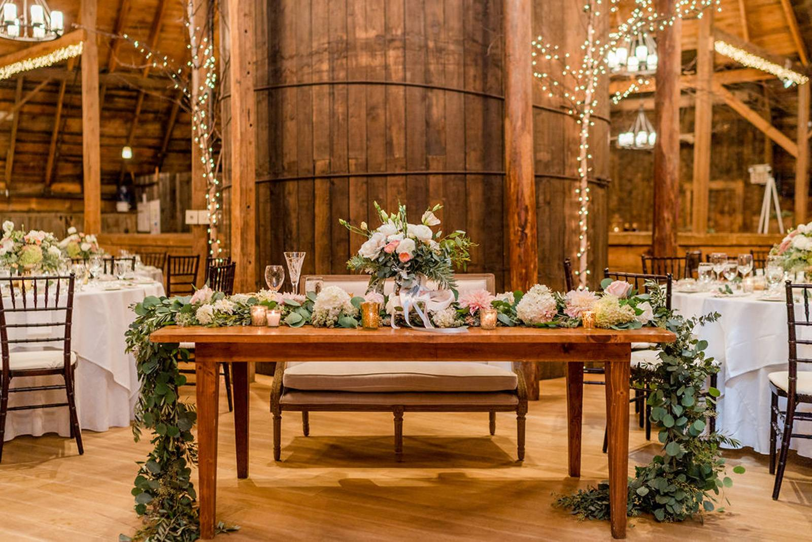 Sweetheart table with floral garland at the Inn at the Round Barn Farm