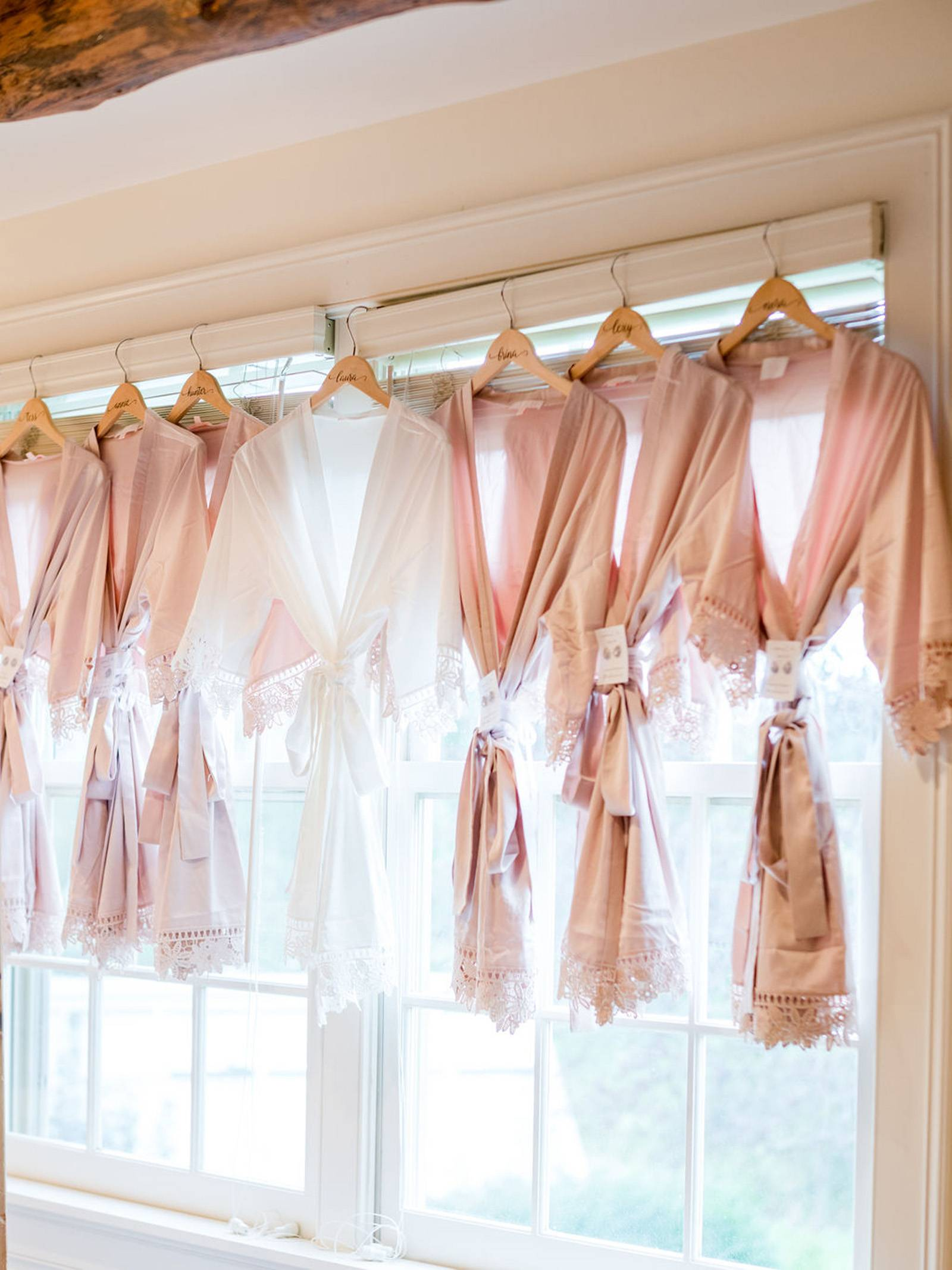 Blush bridesmaid robes handing in window on wedding day