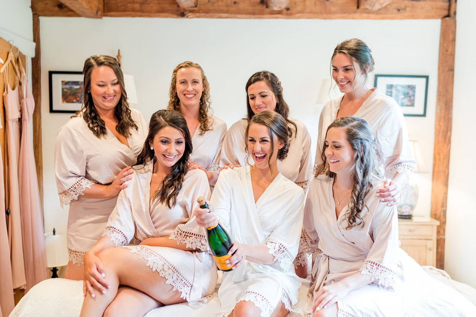 Bride and bridesmaid sitting on bed and popping champagne