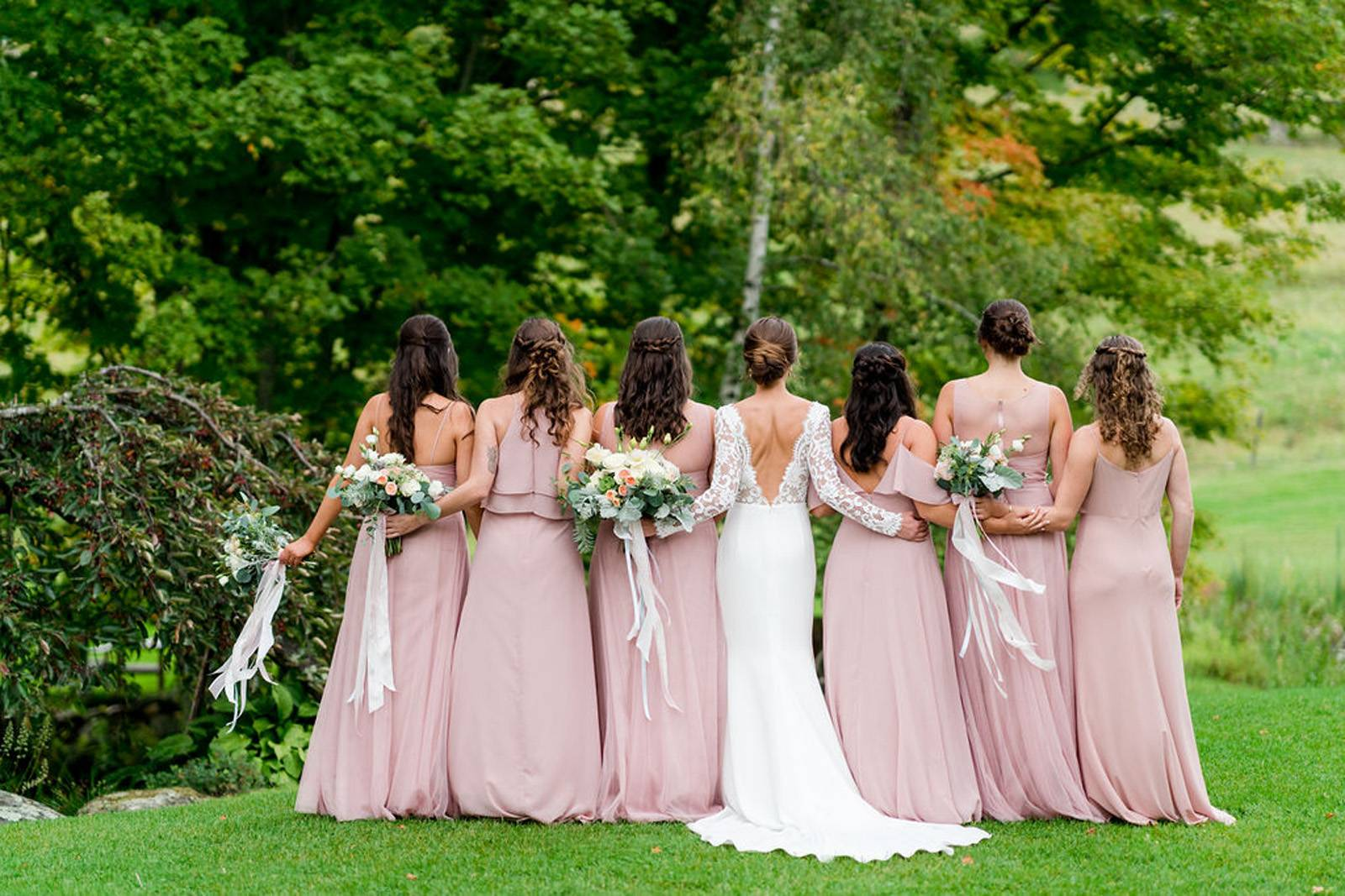 Bride with bridesmaids in blush dresses with bouquets