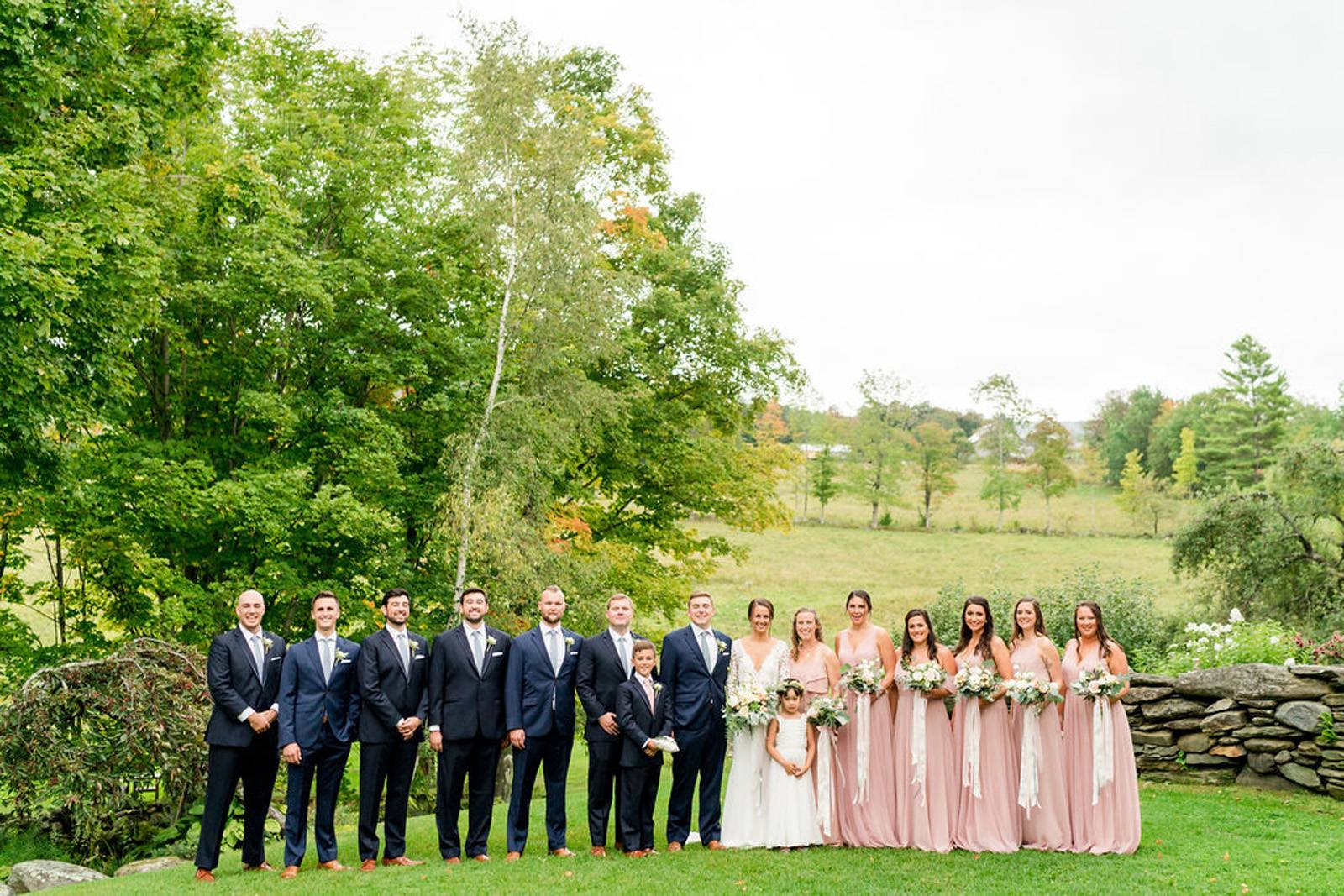 Bridesmaids in blush and groomsmen in navy with bride and groom on wedding day at the Inn at the Rou