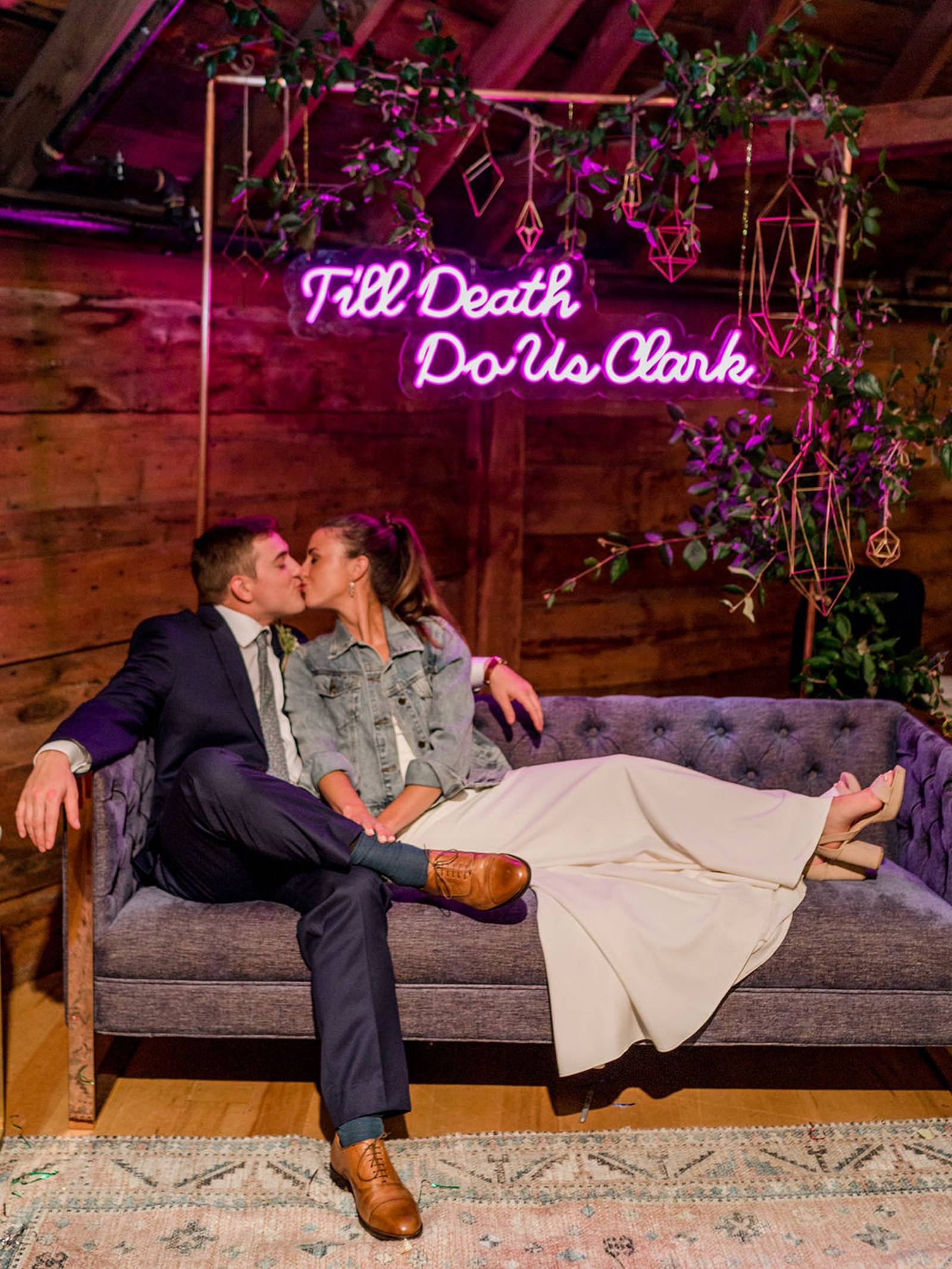 Couple sitting on lounge furniture under custom wedding hashtag neon sign at the Inn at the Round Ba