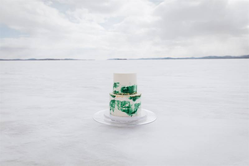 North Country Cakes white and green wedding cake with gold details on frozen Lake Champlain