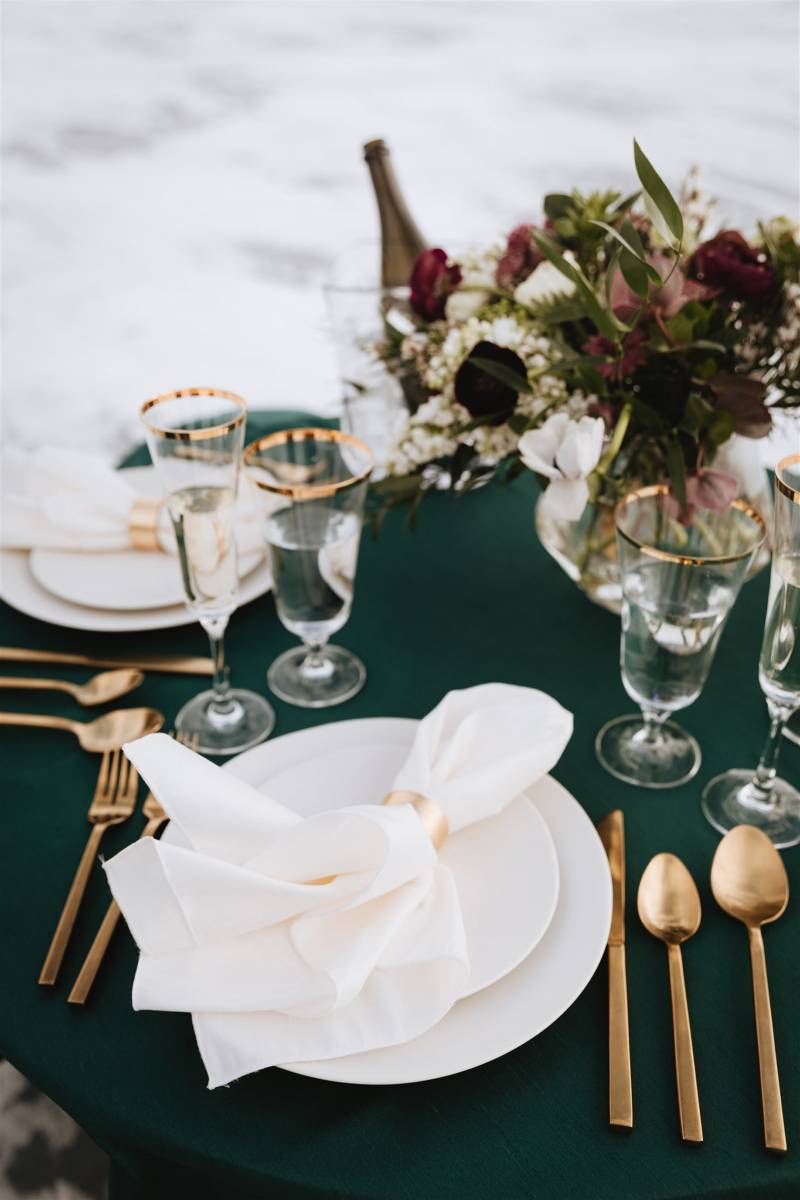 Dark green table setting with lush dark florals and gold flatware