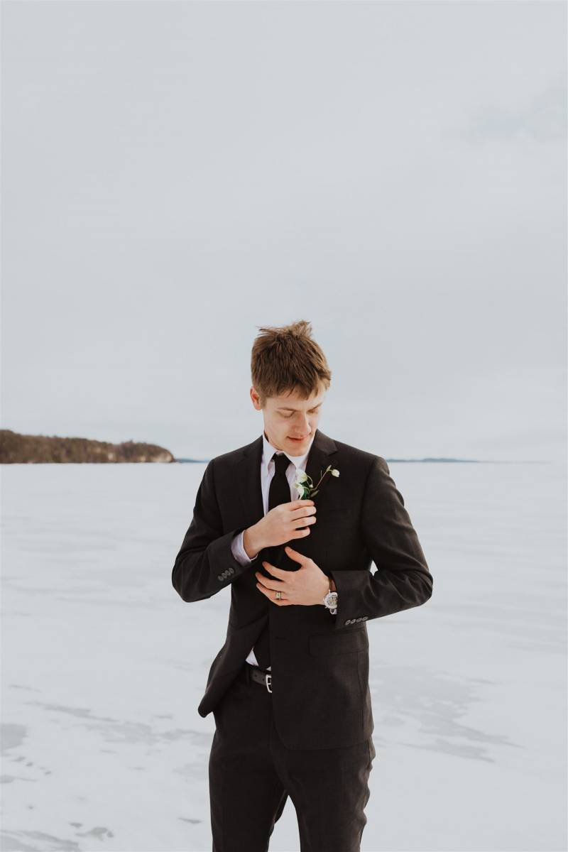 Groom in black suit for winter elopement