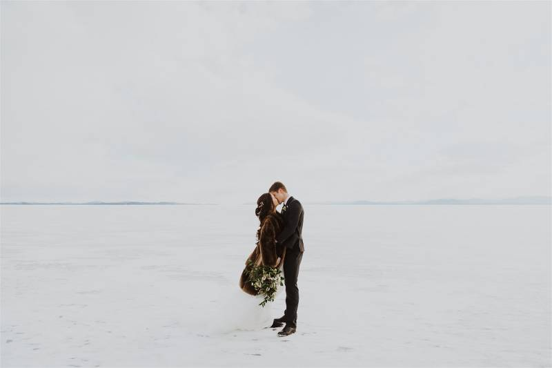 Bride and groom kissing on frozen lake Champlain; bride wearing fur coat