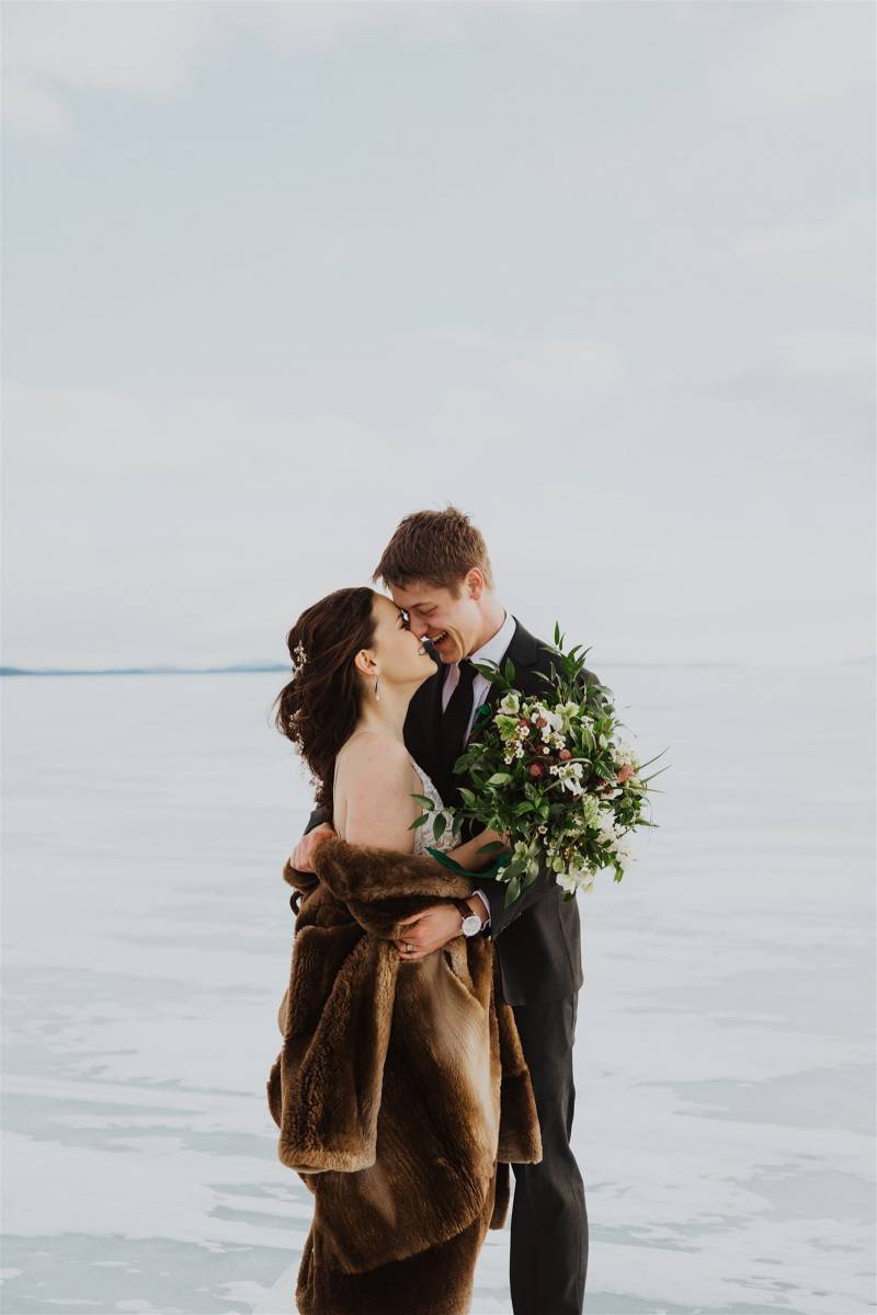 Bride and groom on frozen lake Champlain featuring fur coat and moody lush floral bouquet