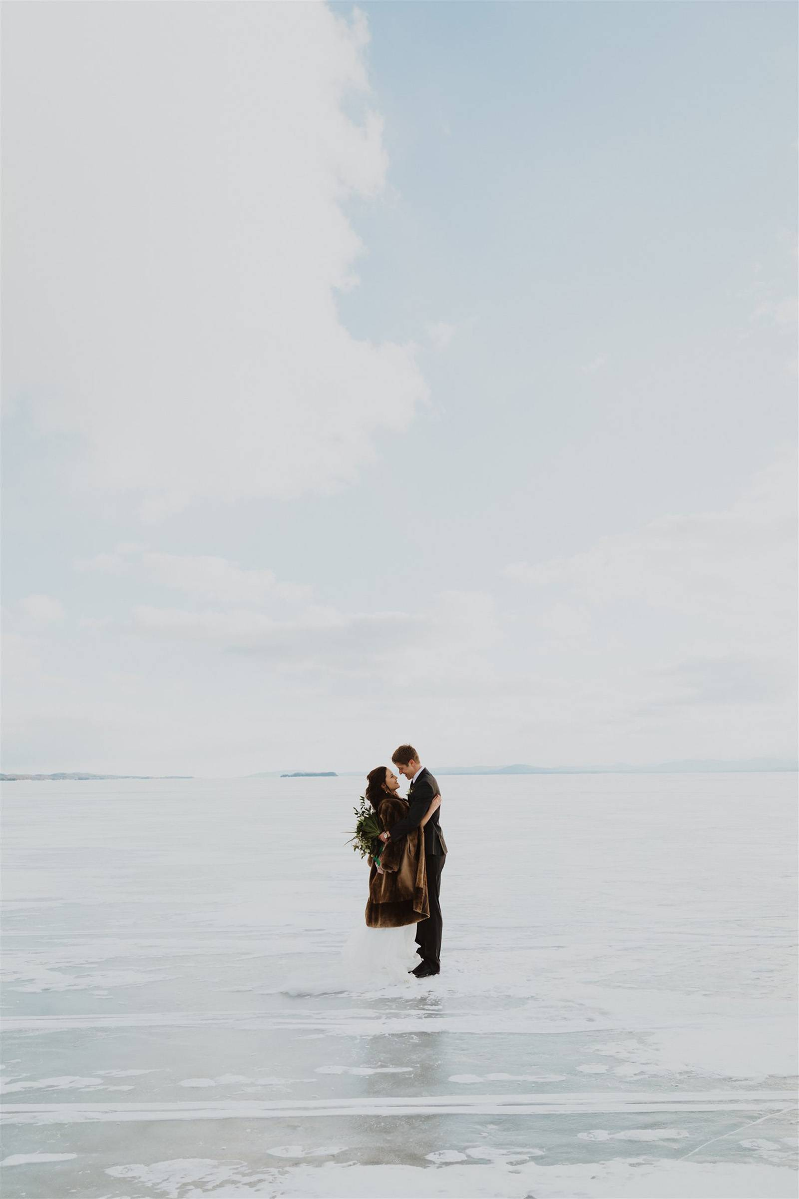 Couple standing on frozen Lake Champlain during winter elopement