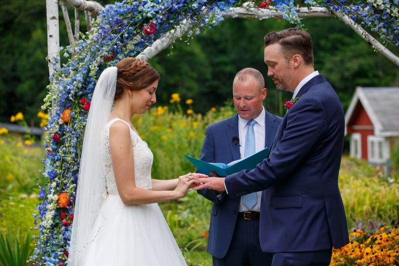 Bride and groom in front of blue floral archway during spring outdoor wedding ceremony in Vermont