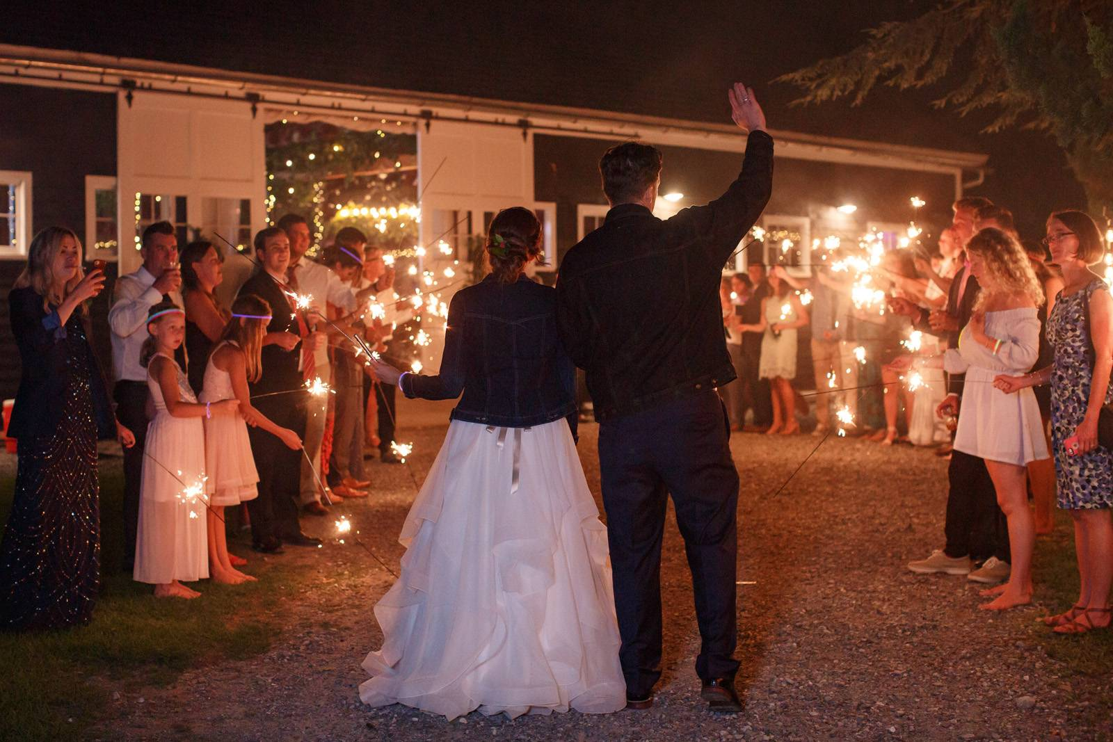 Bride and groom sparkler exit with bridal denim jacket