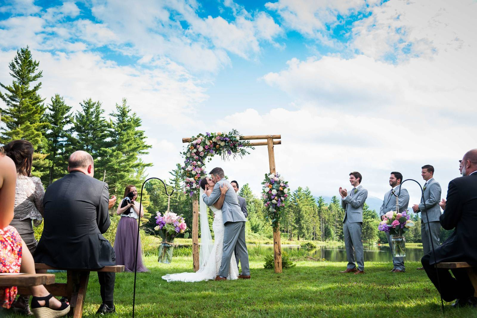 Couple kissing under ceremony arch at Sterling Ridge Resort in Jeffersonville Vermont