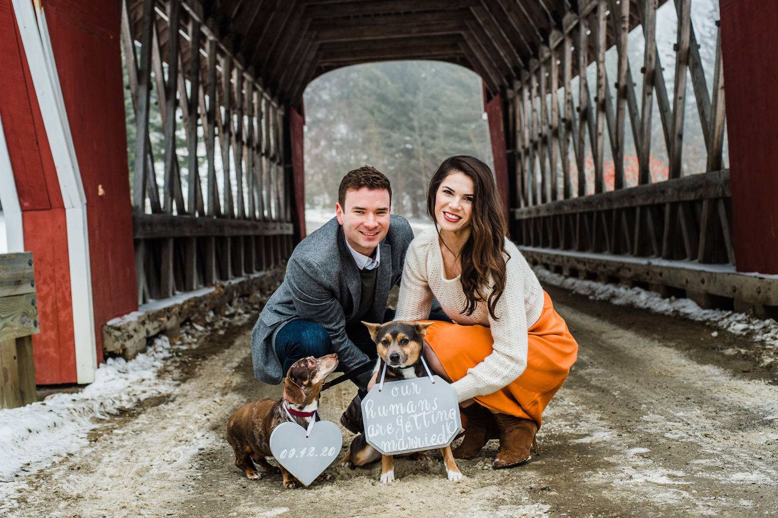 Engaged couple poses with dogs for photo with sign of their wedding date