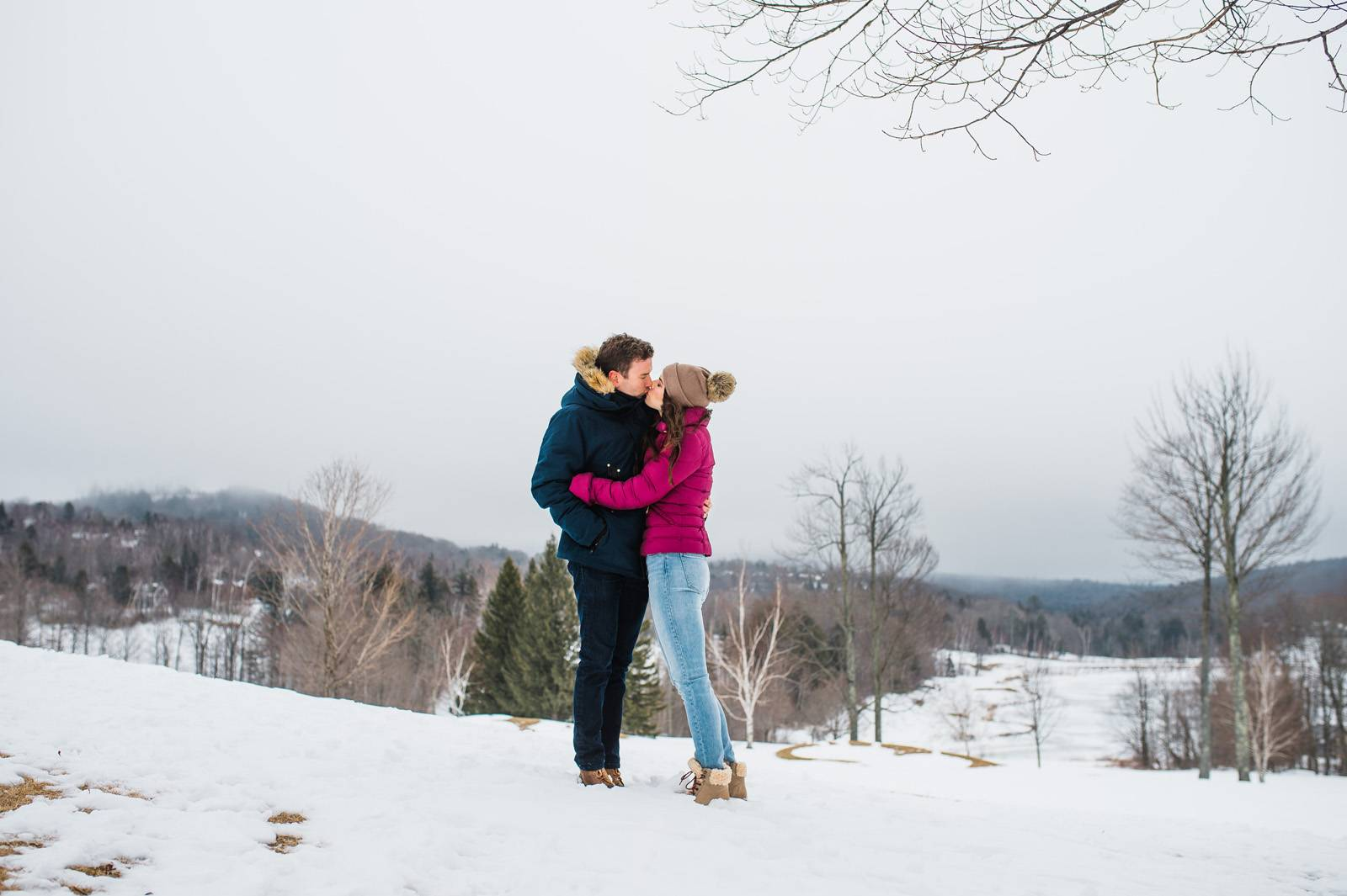 Couple sharing a kiss in parkas during winter engagement session in Stratton Vermont