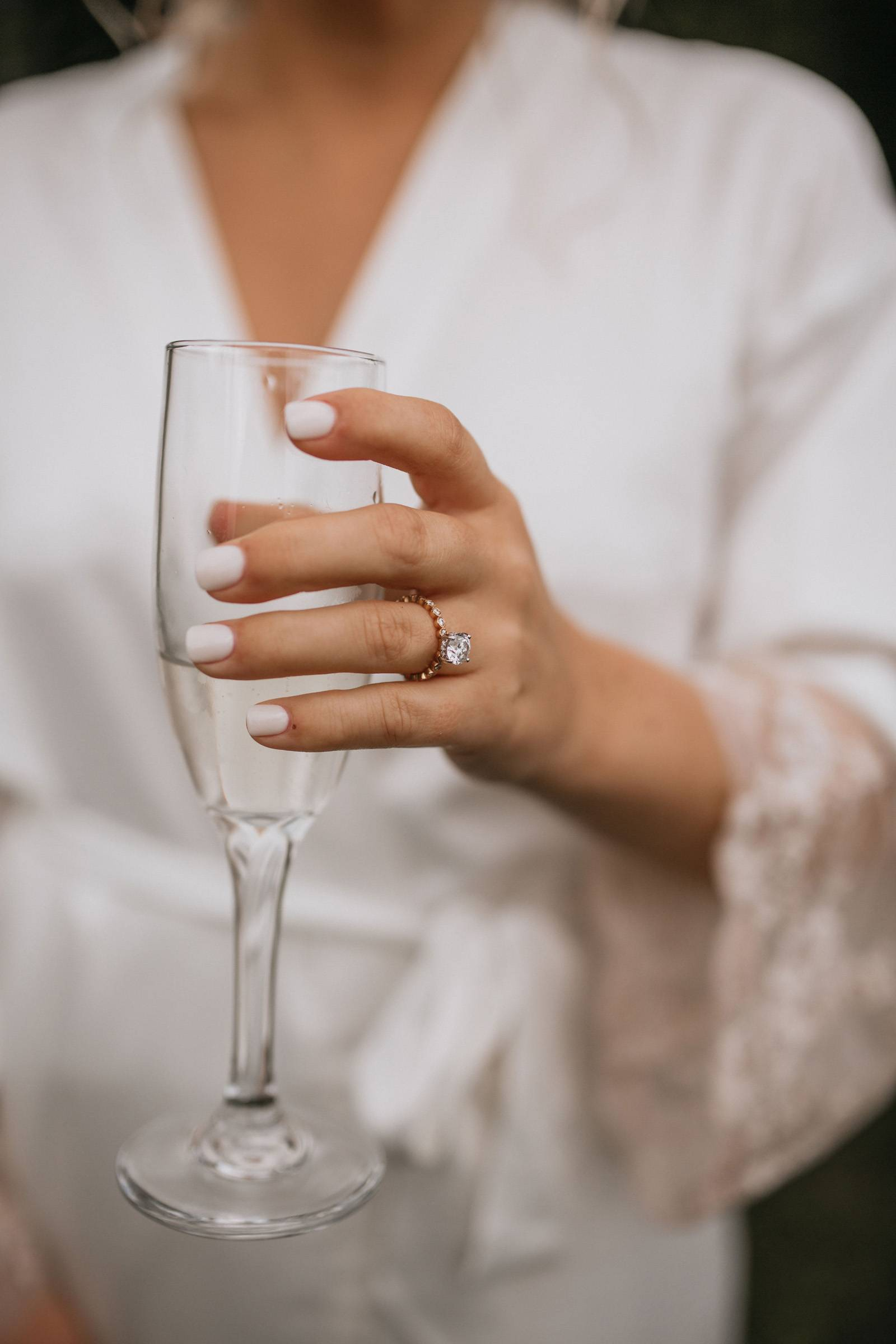 Close up of white bridal manicure and diamond ring with champagne flute
