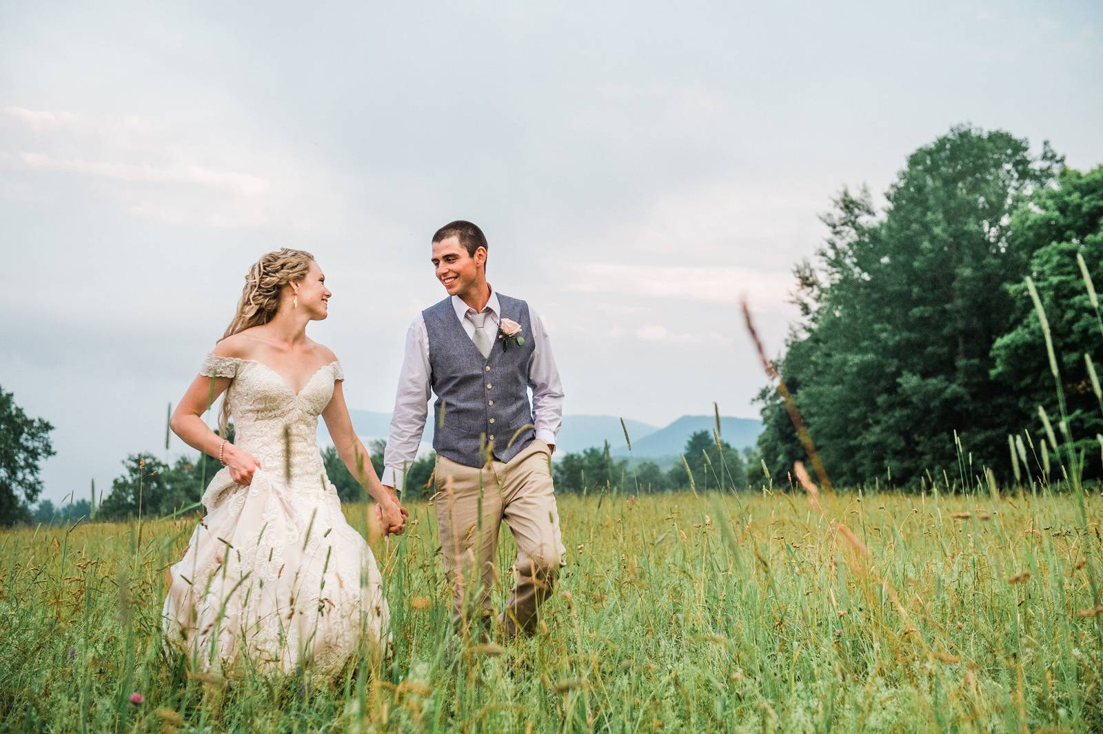 Couple walking through field on wedding day