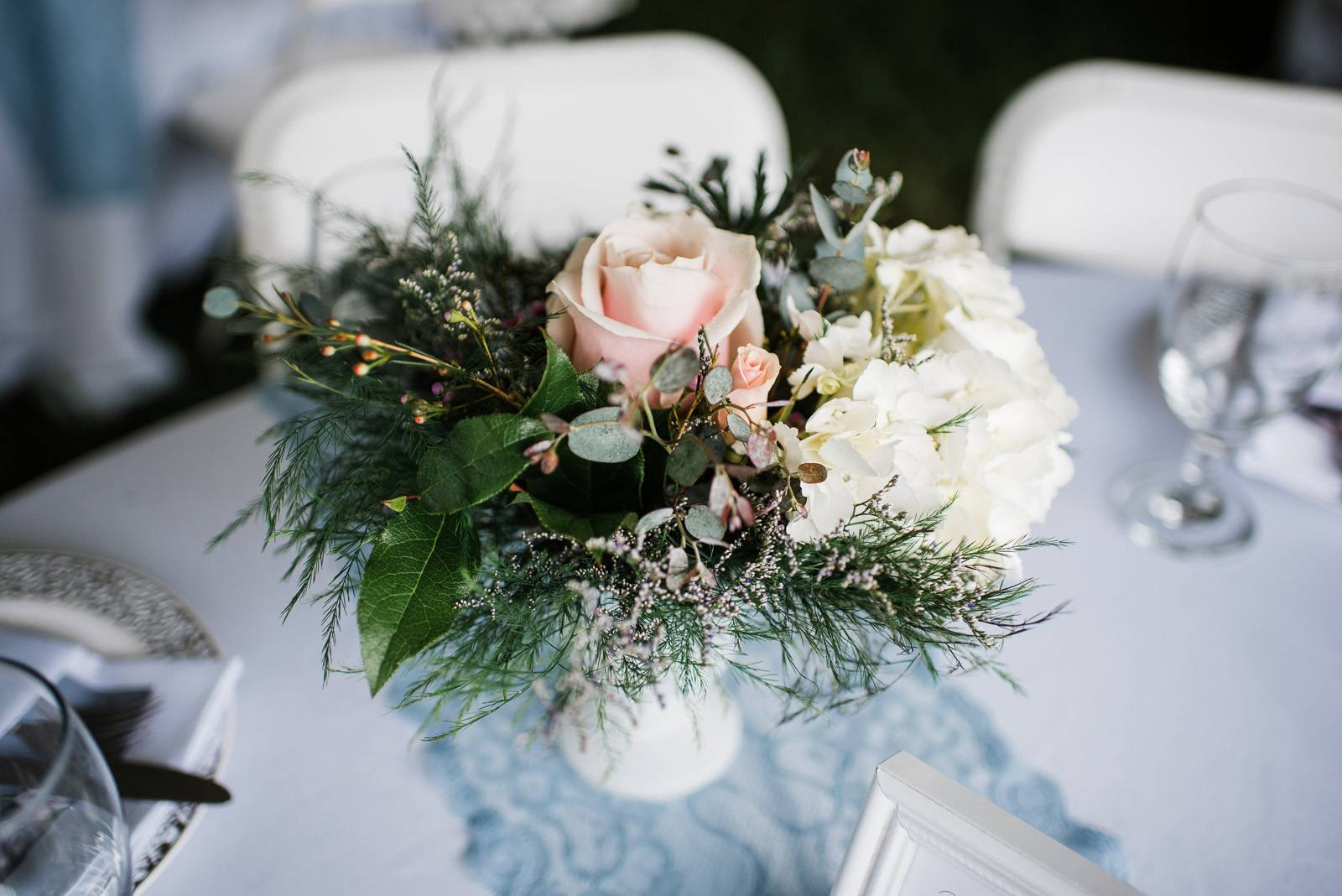 Pink white and greenery centerpieces in milk glass vases