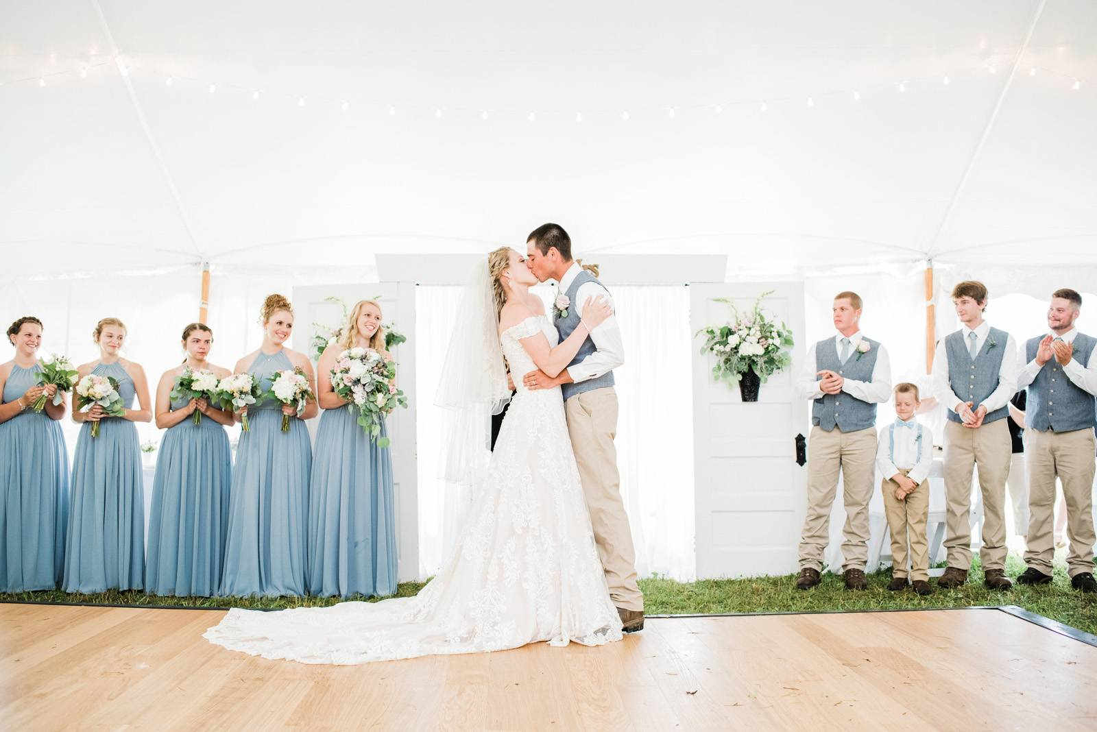 Couple kissing during summer tented ceremony with custom door backdrop