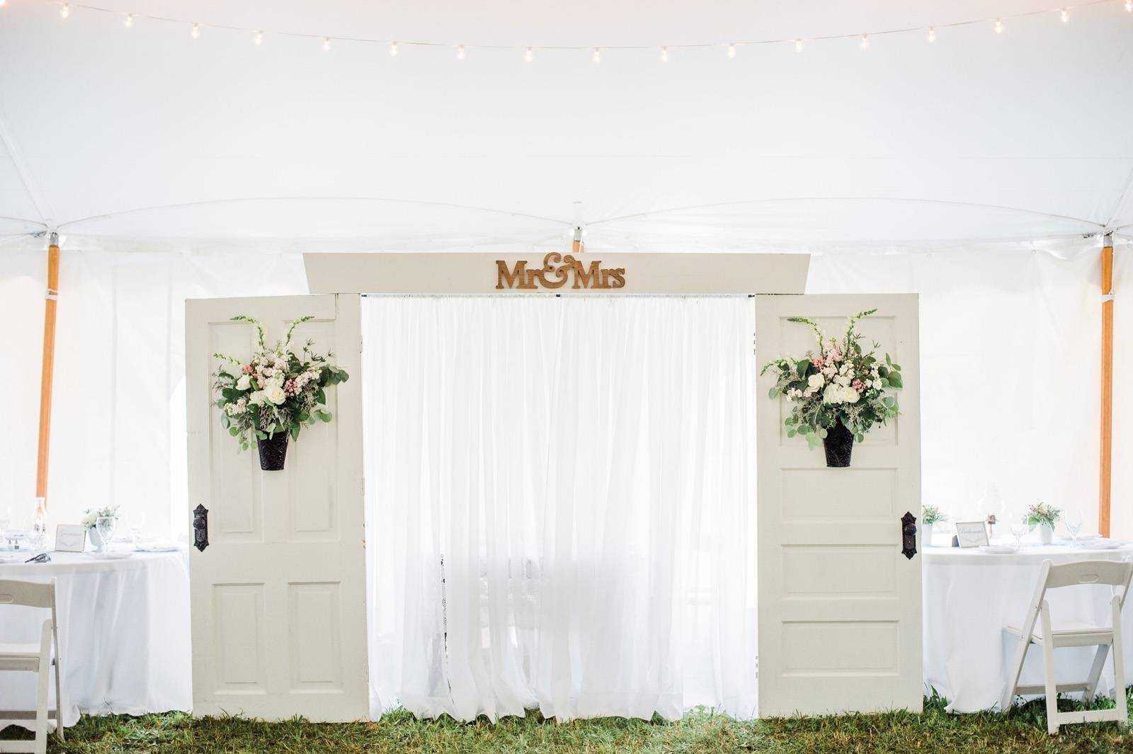 Ceremony backdrop featuring white doors for tented ceremony