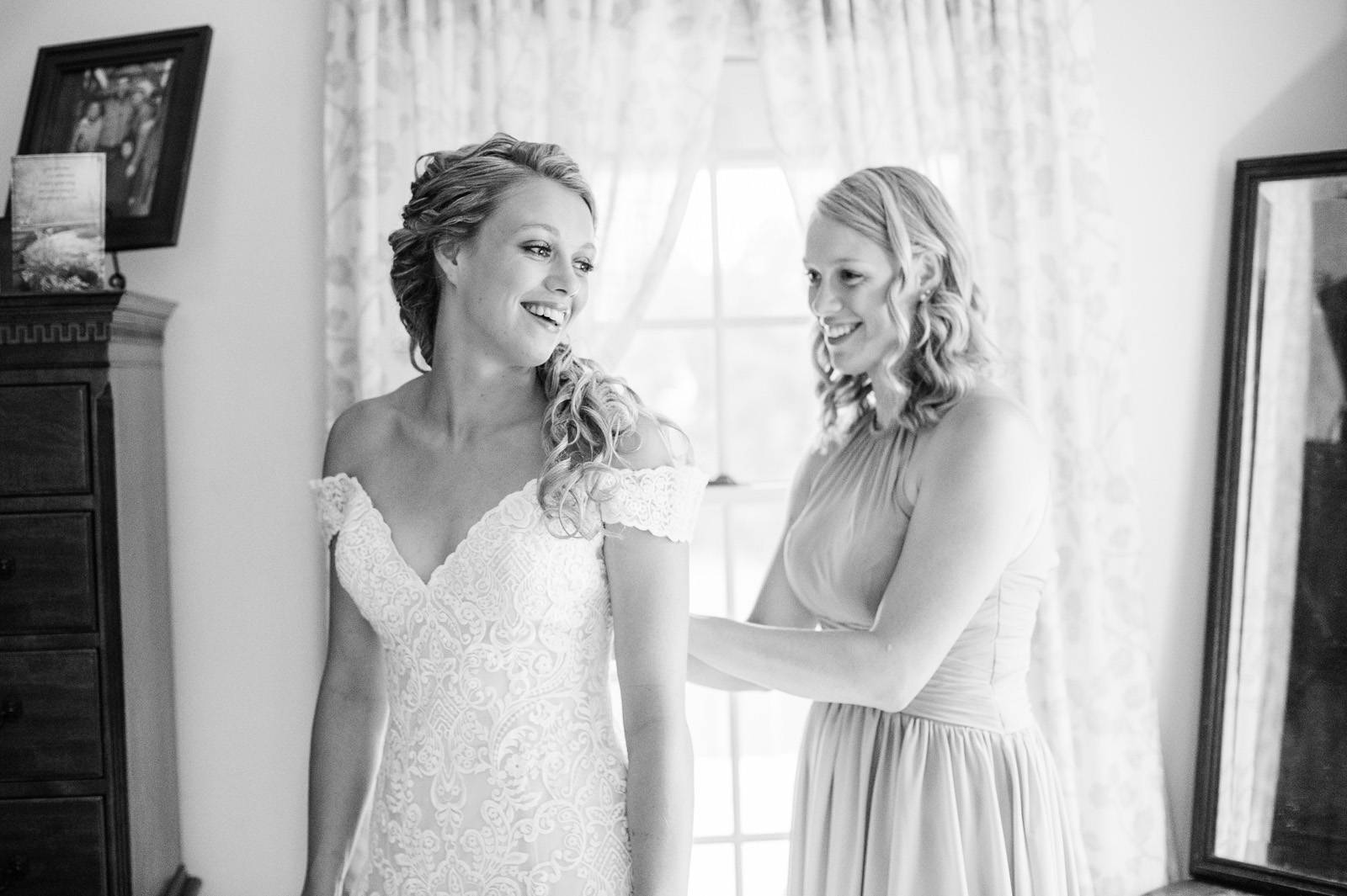 Black and white picture of bride putting on wedding dress on wedding day