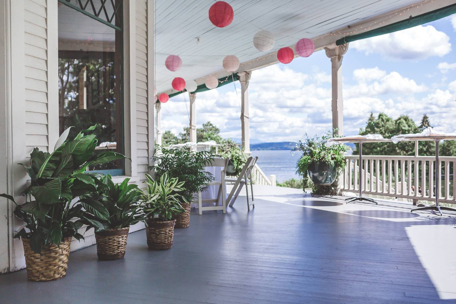Tropical plants and hanging paper lanterns decorate the porch at the Grand Isle Lake House