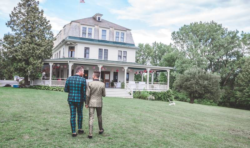 Couple walking toward the Grand Isle Lake House porch after ceremony