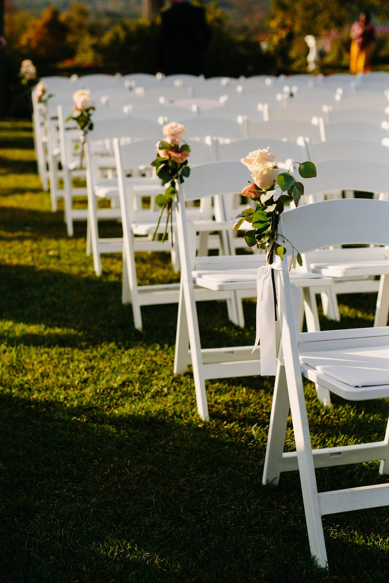 Roses tied onto aisle chairs for outdoor fall black tie wedding ceremony at Hildene