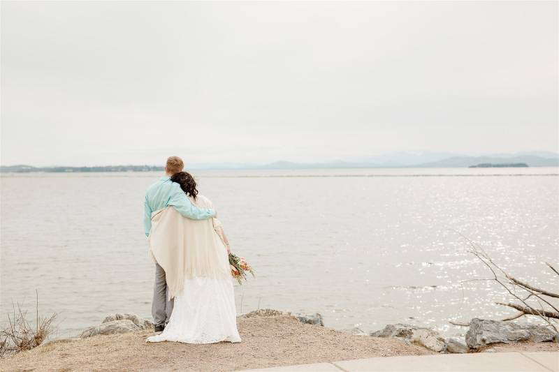 Bride and groom looking over Lake Champlain after lakefront elopement ceremony