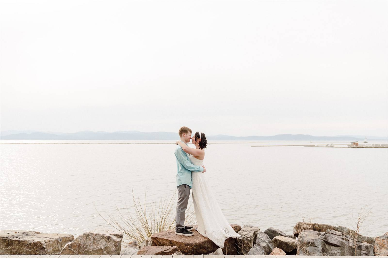 Couple standing on rock in lake at Burlington's waterfront park after elopement
