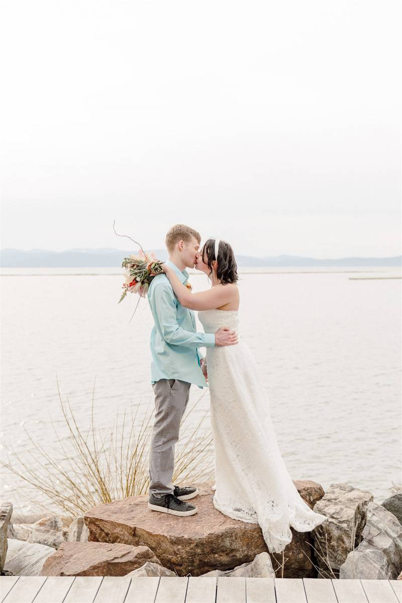 Couple kissing on rock over lake in Burlington after elopement