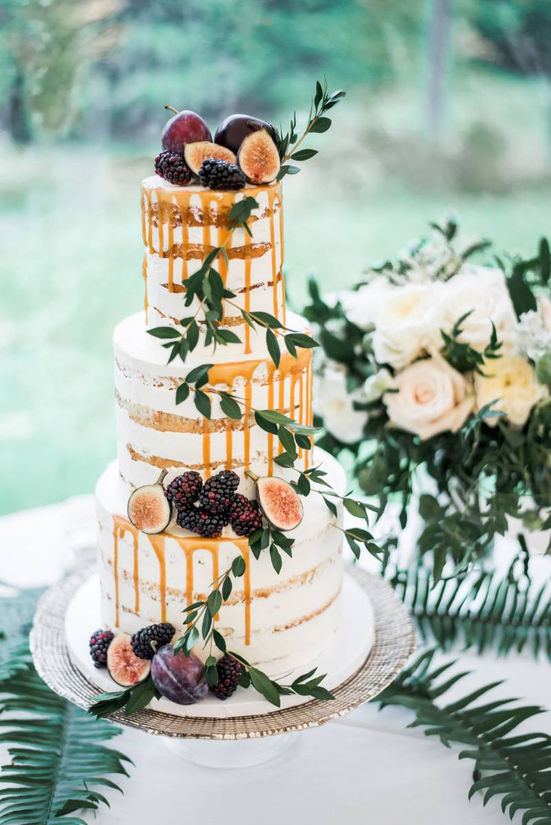Naked wedding cake with fresh fruit and caramel drip design