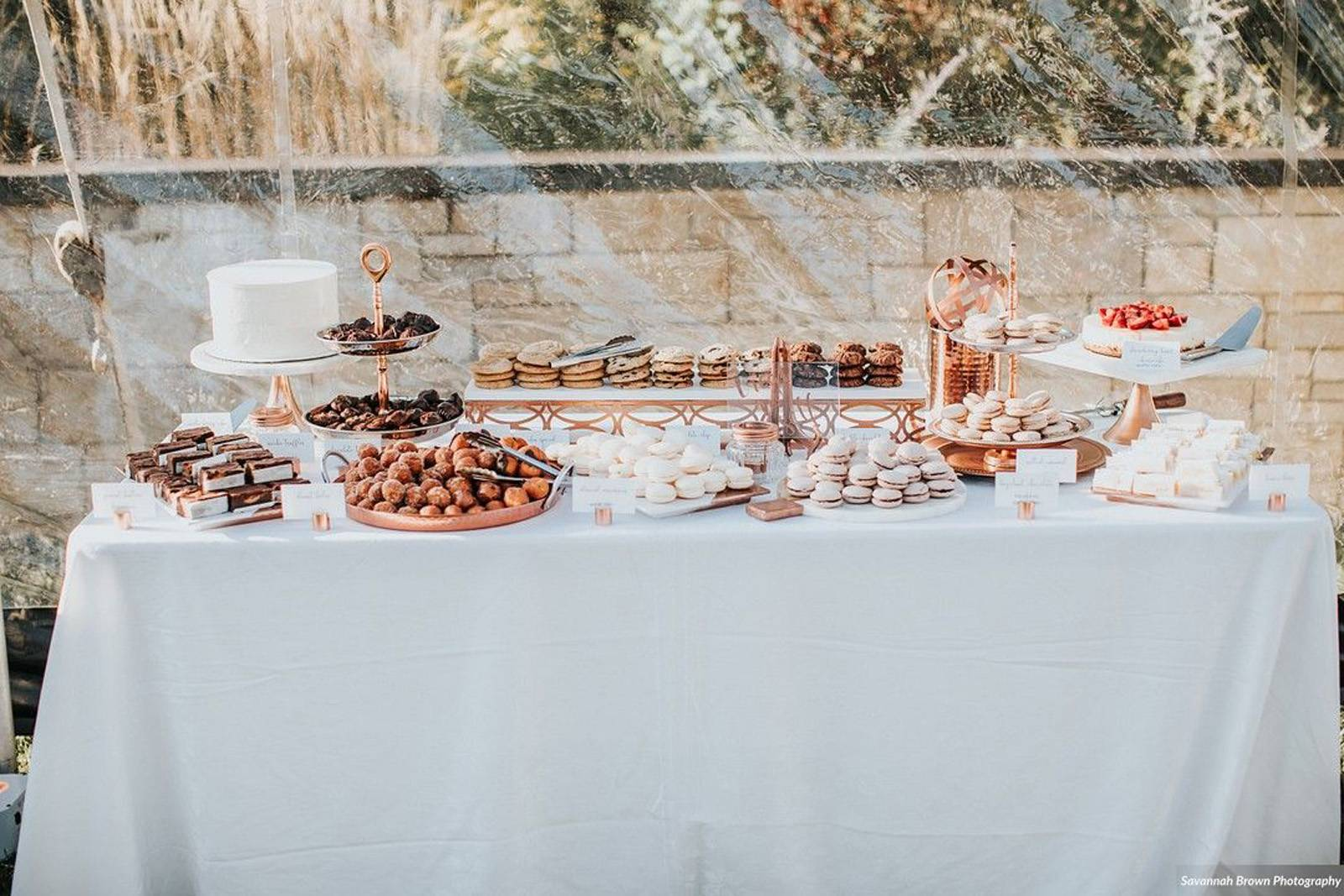 Dessert table set with various desserts by North Country Cakes at a tented reception