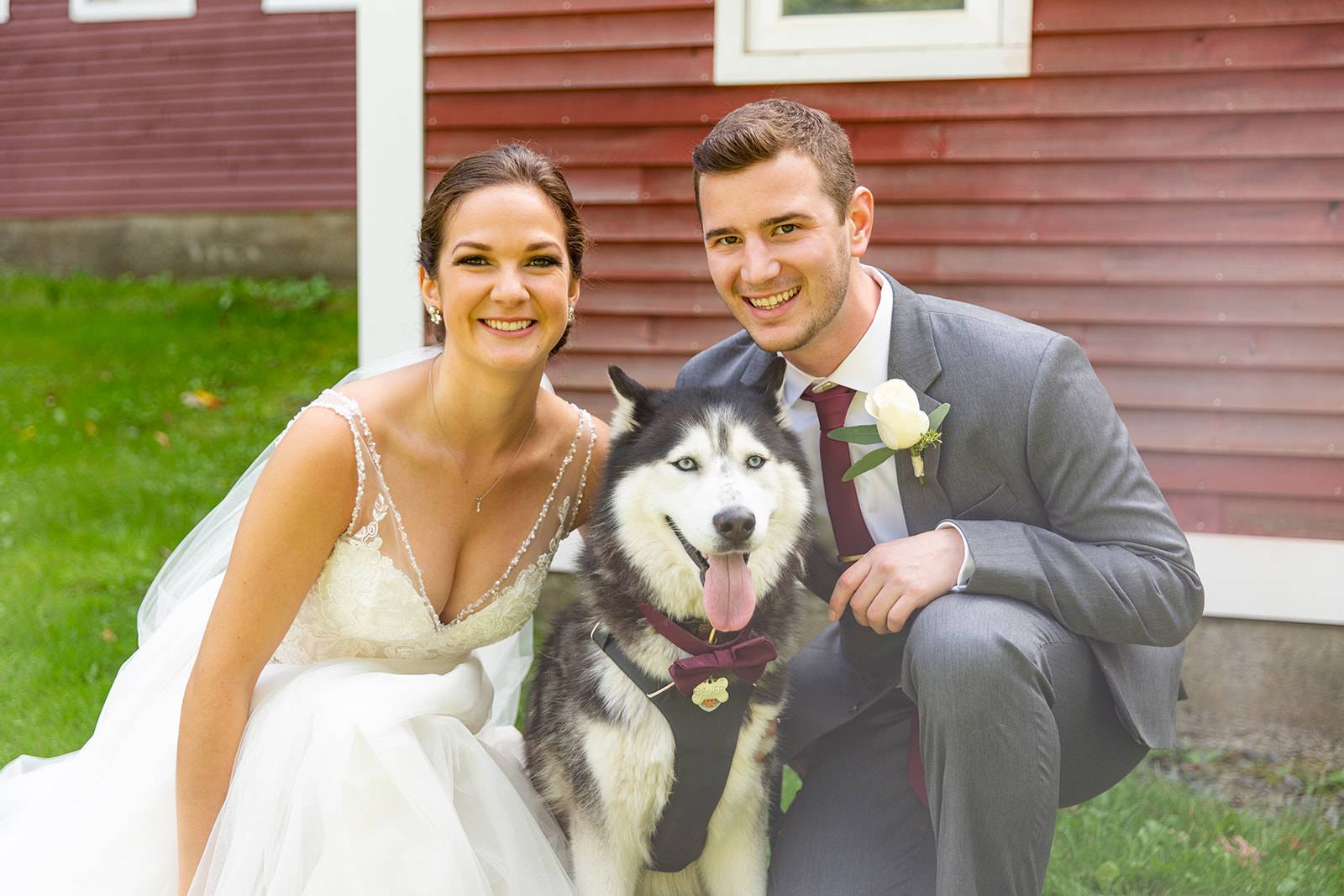 Bride and groom portrait with husky dog wearing bow tie on wedding day
