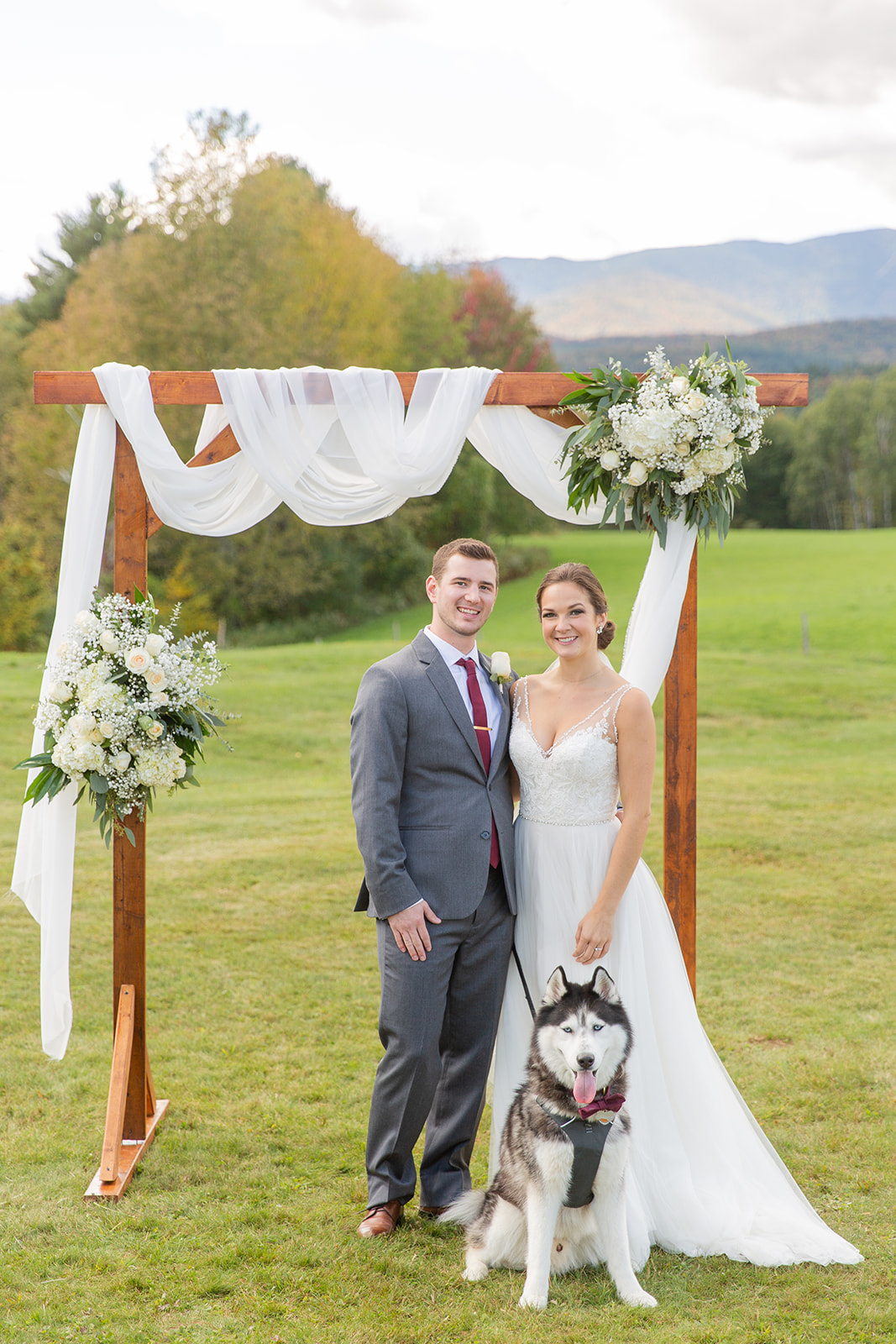 Bride and groom pose under wedding arch with their dog on wedding day