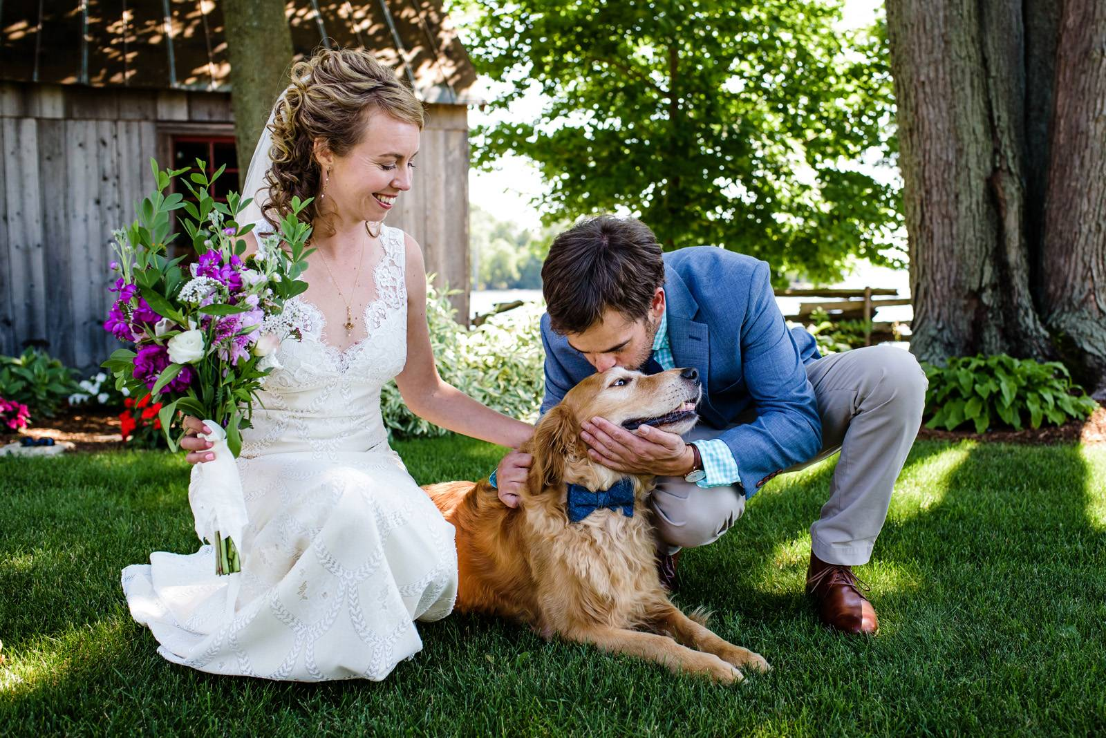 Couple posing with golden retriever dog wearing bow tie on wedding day