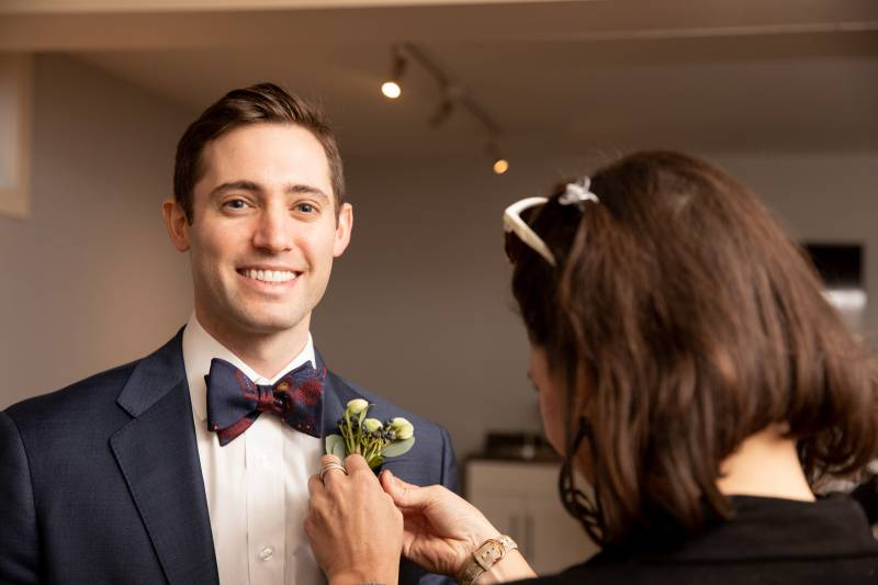 Mother of groom pining boutonnière on smiling groom