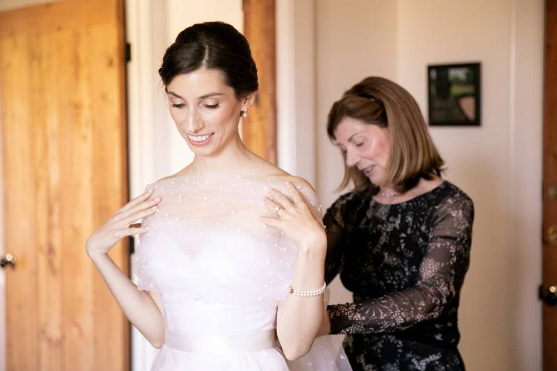 Bride's mom helping bride put on sheer shawl for fall outdoor wedding over strapless ballgown