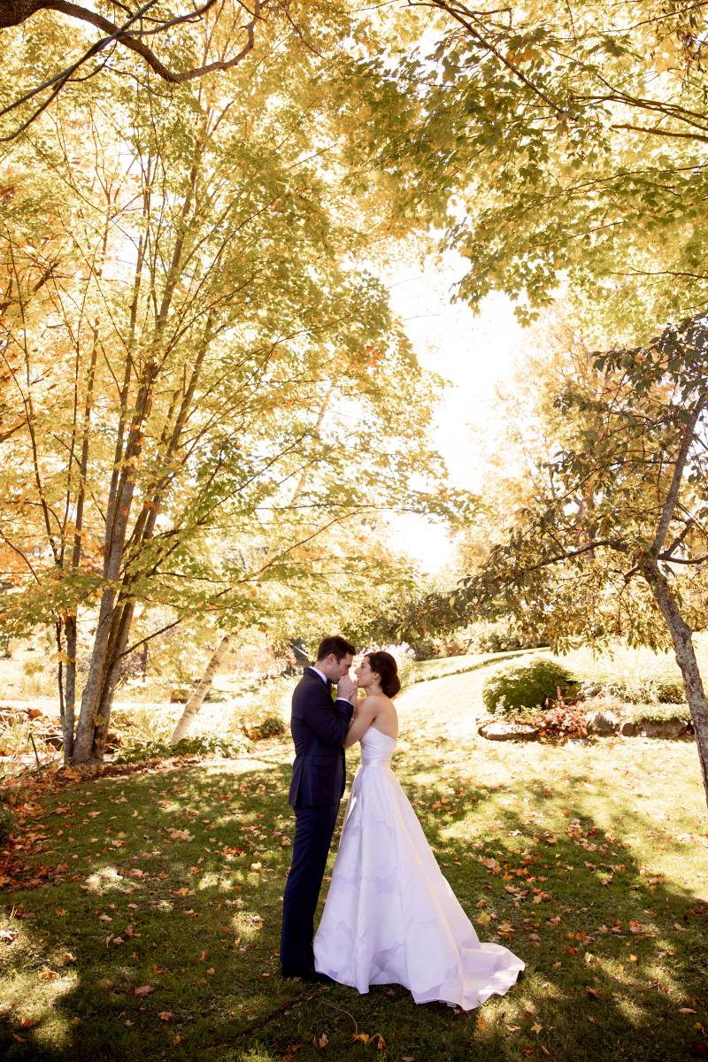 Bride and groom standing under trees with fall foliage during fall wedding in Waitsfield Vermont