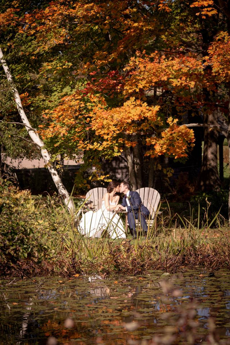 Bride and groom kissing in Adirondack chairs on fall wedding day at the Inn at the Round Barn Farm i