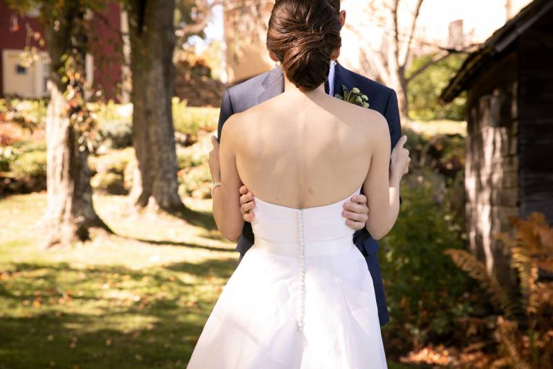 Classic chignon bridal updo with strapless wedding dress with button details