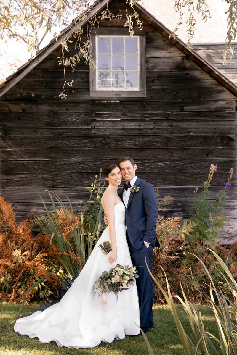 Classic bride and groom smiling in front of barn on fall wedding day