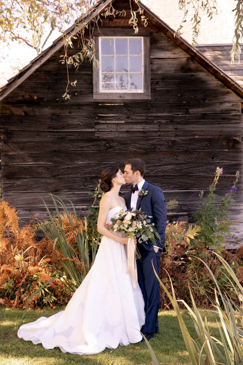 Classic bride and groom kissing portrait in front of rustic barn on Vermont wedding day at the Inn a