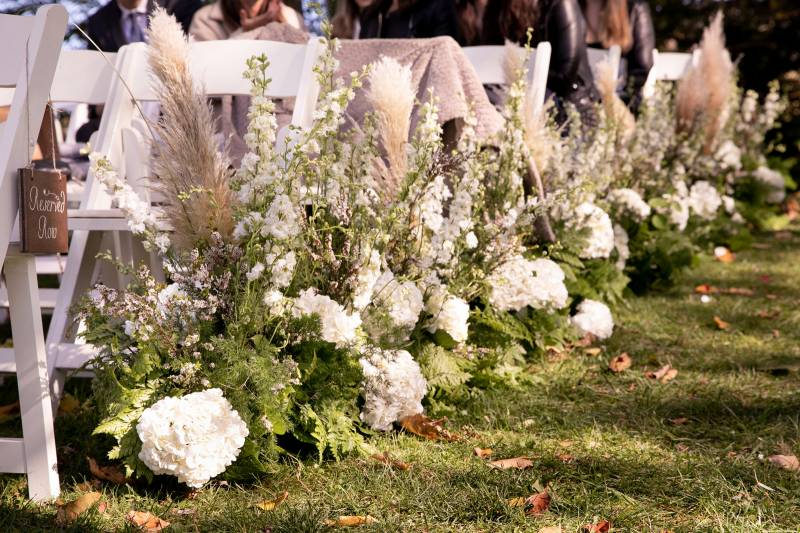White floral aisle details for outdoor ceremony during fall wedding at the Inn at the Round Barn Far