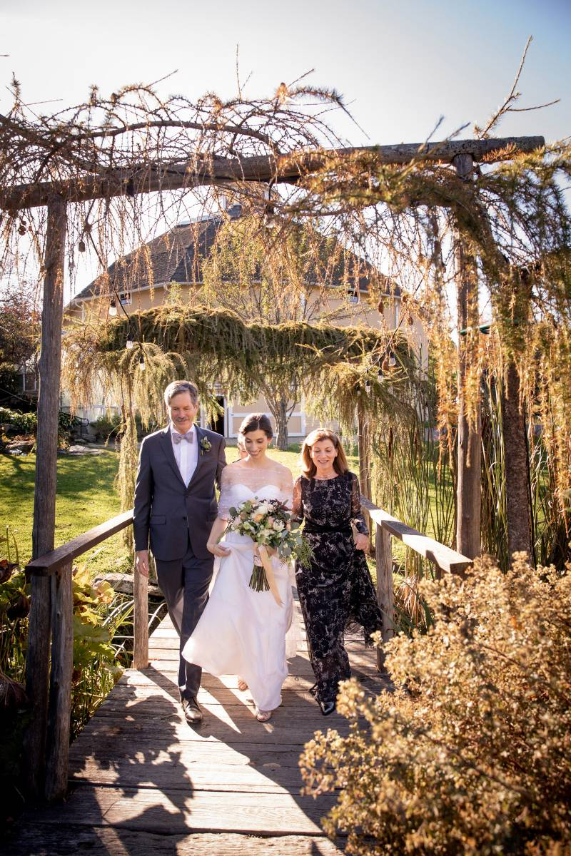 Bride wearing a sheer shall over strapless gown escorted by parents across the bridge at the Inn at
