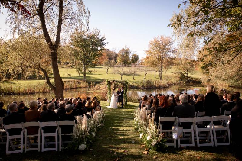 Floral archway set for outdoor ceremony by the pond at the Inn at the Round Barn Farm in Waitsfield