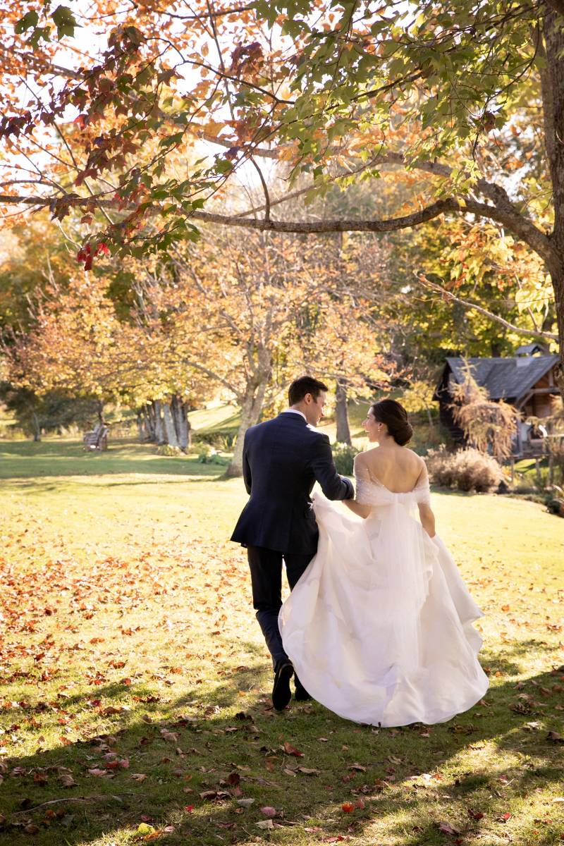 Bride and groom walking under tree after ceremony on fall wedding day in Vermont