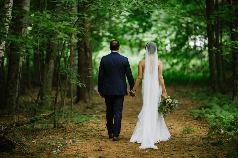 Bride and groom walking on wooded path on wedding day