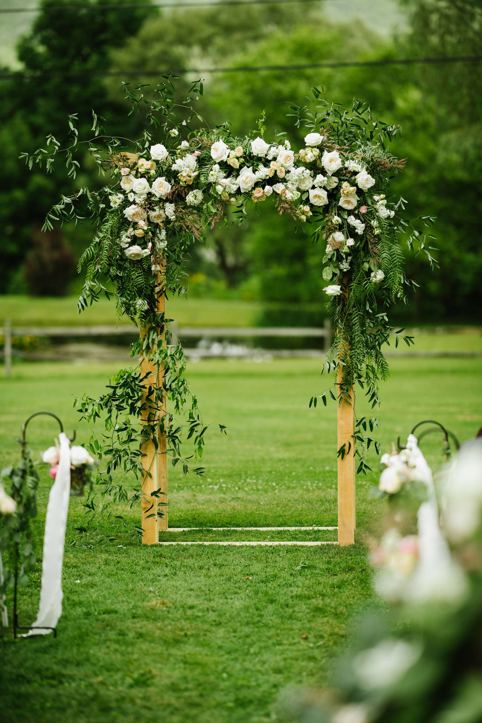 White floral ceremony arch for outdoor summer wedding