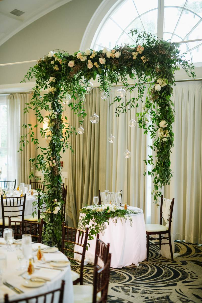 White floral archway with glass hanging candles over sweetheart table during summer wedding at The E