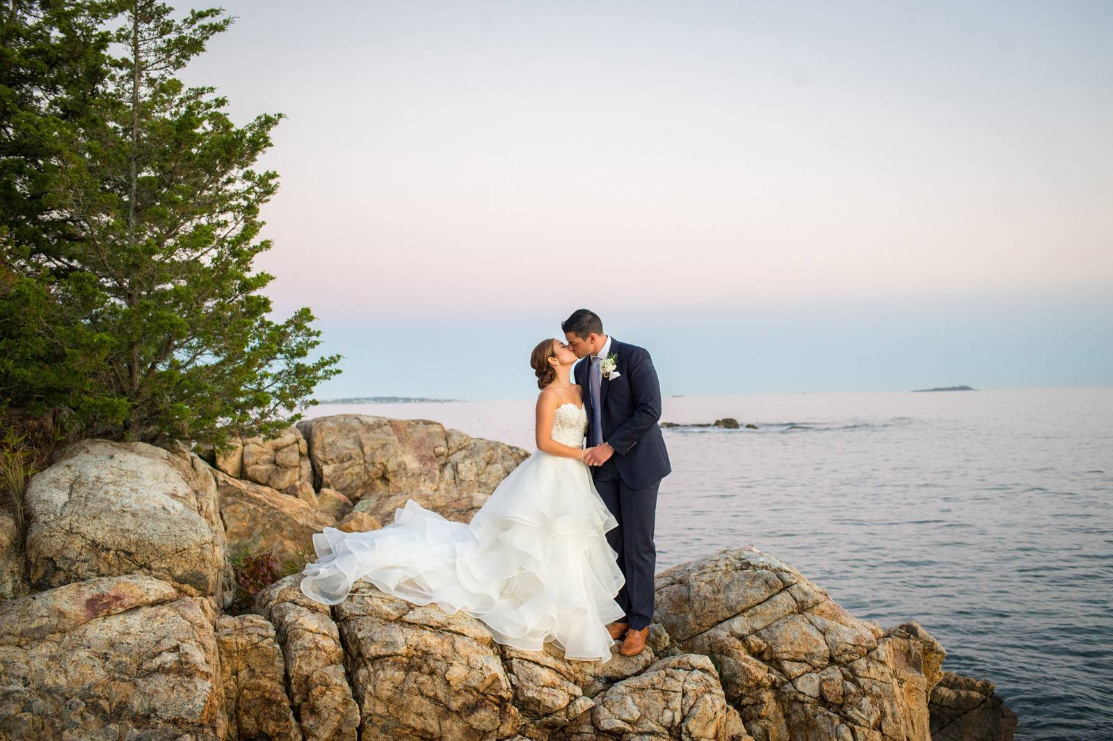 Bride and groom kissing on rock ledge at the lake on wedding day