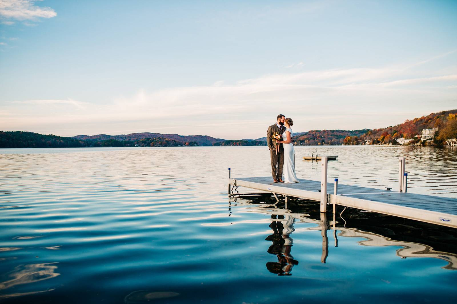 Bride and groom kissing at dock's edge on wedding day